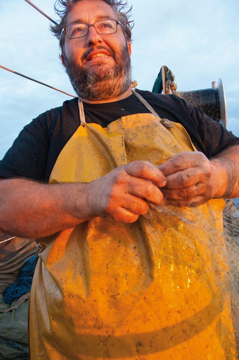 Fischer schaut in den Sonnenaufgang