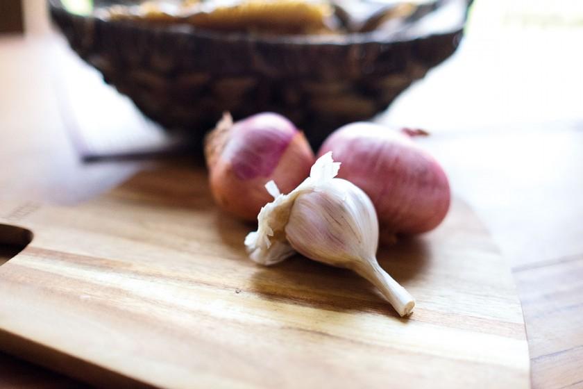Knoblauch und Zwiebeln zum Lammbraten geben