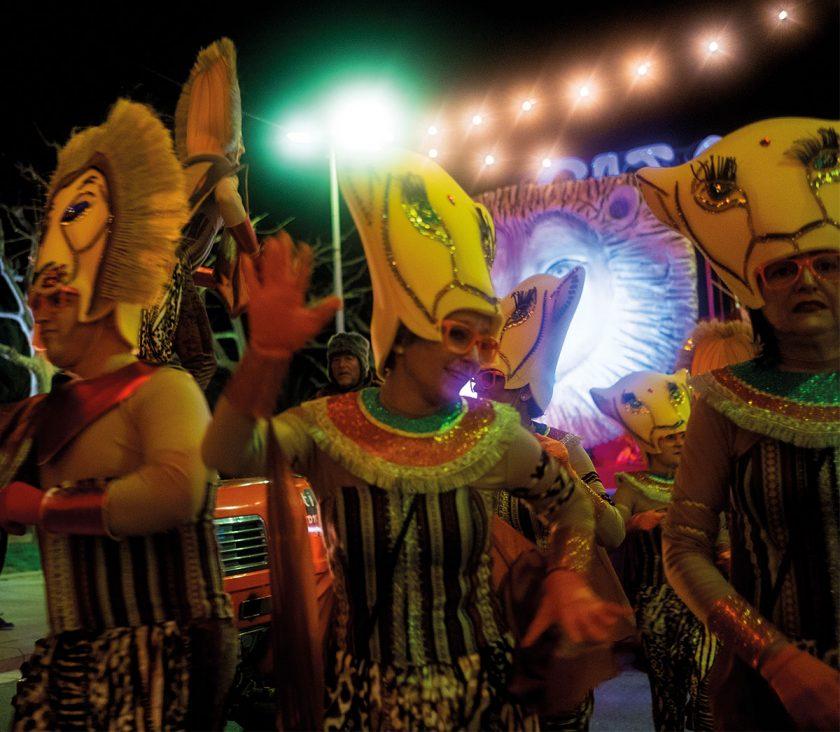 In schrägen Kostümen und lauter Musik feiern die Menschen ausgelassen ihren Karneval.